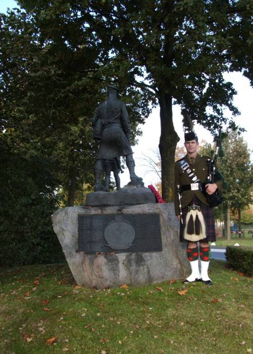 Piper Peter Grant of The Highlanders, standing at the Highland Division memorial at Schijndel, Holland, October 2009. The 65th Anniversary of Liberation.
