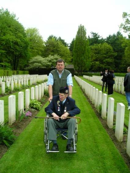 Peter van der Krabben ecorting George Sands along the rows of headstones, Reichswald Forest war cemetery, Germany