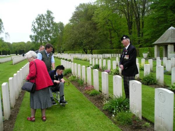 George Sands reading the name of a fallen Cameron. Reichswald war cemetery, Germany